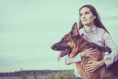 Menina bonita nova com um pastor alemão que joga no gramado Foto de Stock Royalty Free