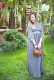 Menina bonita nova com uma cesta com os ovos da páscoa na árvore da Páscoa do fundo Foto de Stock Royalty Free