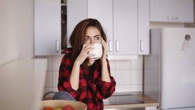 A menina bonita nova começa chamar alguém ao sentar-se em sua cozinha e ao comer um copo do chá em sua mão filme