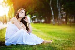 A menina bonita nova de sorriso está sentando-se na grama foto de stock