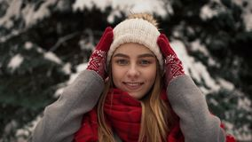Menina bonita nova dentro na roupa morna que está perto das árvores de Natal, vestindo um chapéu e olhando na câmera vídeos de arquivo