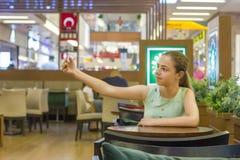 A menina bonita nova do adolescente toma o selfie em um café no shopping imagem de stock
