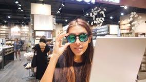Menina bonita nova do moderno da raça misturada que tenta óculos de sol retros no shopping 4K vídeos de arquivo
