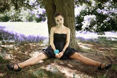 Menina bonita nova do retrato que senta-se sobre a árvore com doces do pirulito Imagem de Stock