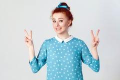 Menina bonita nova do ruivo com vestido azul e a faixa principal que mostram o sinal de paz foto de stock royalty free