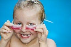Menina bonita nova em googles da terra arrendada do swimming-pool Foto de Stock Royalty Free