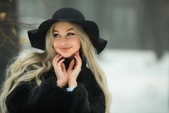 Menina bonita nova em um casaco de pele preto fotos de stock