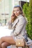 Menina bonita nova em um revestimento bege, chamando pelo telefone, sentando-se Fotografia de Stock