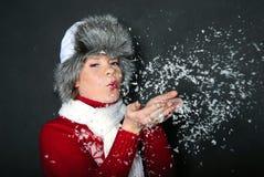 A menina bonita nova em um tampão purga a neve Foto de Stock