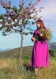 Menina bonita nova em um vestido cor-de-rosa brilhante com um ramalhete do YE Imagens de Stock Royalty Free