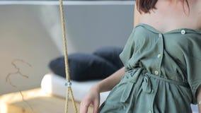 Menina bonita nova em um vestido verde que senta-se em um balanço e que mostra seu corpo macio video estoque