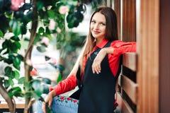 Menina bonita nova em uma camisa vermelha e em um revestimento sem mangas longo que sentam-se sobre em um banco de madeira com co Imagem de Stock