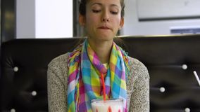 A menina bonita nova está bebendo um cocktail em um café Está feliz filme