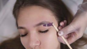 A menina bonita nova está encontrando-se no sofá durante o tratamento dos eyebrowes na beleza do estúdio, esteticista que depila  vídeos de arquivo