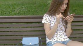 A menina bonita nova está sentando-se em um banco de parque, olhando sms em um smartphone Obteve más notícias de meu noivo vídeos de arquivo