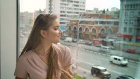 A menina bonita nova está sentando-se na janela, cabelo tocante, olhando na câmera, sonhando o conceito vídeos de arquivo