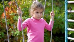 A menina bonita nova está tendo o divertimento em um balanço A criança balança em um balanço da corda 4k, 60fps, movimento lento video estoque