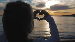 A menina bonita nova faz o coração por suas mãos no sol de ajuste de moldação da forma do coração no por do sol sobre o oceano Co video estoque