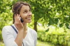 A menina bonita nova feliz está chamando pelo telefone no parque verde do verão Imagem de Stock