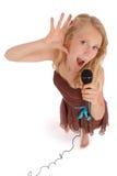 Menina bonita nova feliz que canta com microfone Foto de Stock