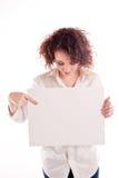 A menina bonita nova guarda um sinal branco vazio para que você preencha Imagens de Stock