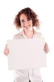 A menina bonita nova guarda um sinal branco vazio para que você preencha Imagem de Stock