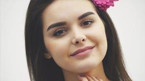 Menina bonita nova bonita isolada no fundo branco Com uma flor cor-de-rosa no cabelo, emoções, cosméticos vídeos de arquivo
