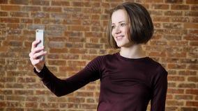 A menina bonita nova manda o vídeo chamar seu smartphone, sorrindo, conceito de uma comunicação, fundo do tijolo vídeos de arquivo