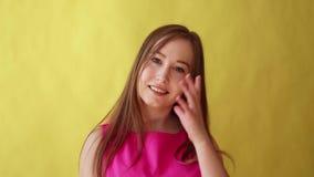 A menina bonita nova mostra o gesto de vinda, namoradeira, conceito de uma comunicação, fundo amarelo vídeos de arquivo