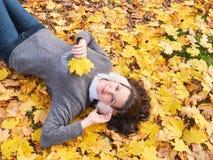 Menina bonita nova na camiseta cinzenta que encontra-se nas folhas amarelas, vista de cima de imagem de stock royalty free