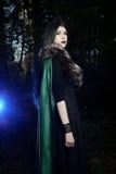 Menina bonita nova na capa de chuva verde, olhares como a bruxa em Dia das Bruxas na floresta escura Foto de Stock