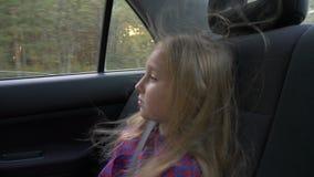 Menina bonita nova na viagem por estrada da aventura dentro do carro o vento em seu cabelo Menina branca consideravelmente séria  vídeos de arquivo