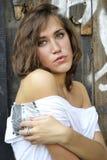 Menina bonita nova no fundo de uma parede de madeira Fotografia de Stock Royalty Free