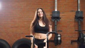 Menina bonita nova no gym, agitando seus pés no simulador do ciclismo, sorrindo na câmera video estoque