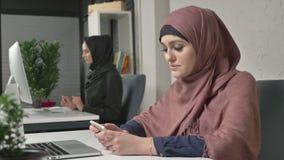 A menina bonita nova no hijab cor-de-rosa senta-se no escritório e usa-se o smartphone Menina no hijab preto no fundo Mulheres ár filme