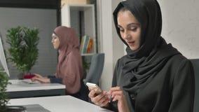 A menina bonita nova no hijab preto senta-se no escritório e usa-se o smartphone Menina no hijab preto no fundo árabe filme