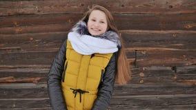 A menina bonita nova no inverno veste o levantamento positivamente na câmera no fundo de uma casa de madeira no filme