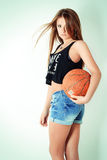 A menina bonita nova no short com a bola está no estúdio no fundo branco Imagens de Stock Royalty Free