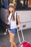 Menina bonita nova no short perto do ônibus com mala de viagem, câmera e bilhetes à disposição Curso Foto de Stock Royalty Free