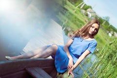 Menina bonita nova no vestido azul que senta-se no barco Imagens de Stock