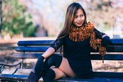 Menina bonita nova no vestido preto com o lenço marrom que senta-se no banco Foto de Stock Royalty Free