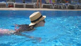 Menina bonita nova nos óculos de sol e na natação do chapéu na associação Mulher que relaxa na água morna clara no dia ensolarado video estoque