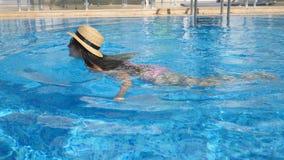 Menina bonita nova nos óculos de sol e na natação do chapéu na associação Mulher que relaxa na água morna clara no dia ensolarado vídeos de arquivo