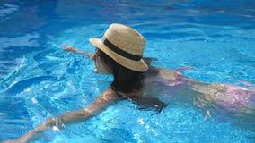 Menina bonita nova nos óculos de sol e na natação do chapéu na associação Mulher que relaxa na água morna clara no dia ensolarado filme
