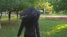 A menina bonita nova que anda e gerencie ao redor no fundo do parque ensolarado do verão filme