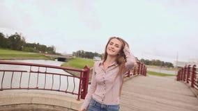 Menina bonita nova que anda na ponte através do lago no parque Canta a música filme