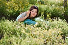 Menina bonita nova que coloca no campo de flores Fotografia de Stock Royalty Free