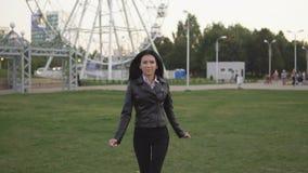 Menina bonita nova que corre à câmera no parque ensolarado do verão filme