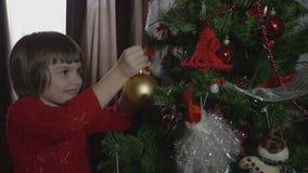 Menina bonita nova que decora a árvore de Natal - 4k vídeos de arquivo
