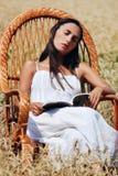 Menina bonita nova que descansa em uma cadeira no campo de trigo imagens de stock royalty free